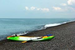 Färgrika kajaker och kanoter på den steniga stranden arkivbild