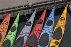 Färgrika kajaker som binds upp på docken Royaltyfria Bilder