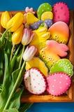 Färgrika kakor för påskkanin och äggi en korg på trälodisar royaltyfri foto