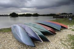 Färgrika kanoter på sjön över molnig och dramatisk himmel royaltyfri bild