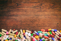 Färgrika kapslar på en träbakgrund Fotografering för Bildbyråer