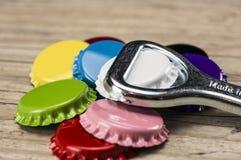 Färgrika kapsyler och flasköppnare Fotografering för Bildbyråer