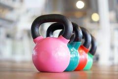 Färgrika kettlebells i idrottshall royaltyfri foto