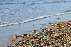Färgrika kiselstenar och bränning på det baltiska havet Royaltyfri Fotografi