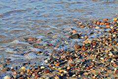 Färgrika kiselstenar och havsbränning Royaltyfri Bild
