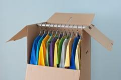 Färgrika kläder i en garderobask för att flytta sig Royaltyfri Foto