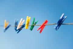 Färgrika klädnypor på klädstreck mot blå himmel Royaltyfri Bild