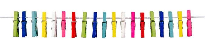 Färgrika klädnypor som hänger på klädstrecket Fotografering för Bildbyråer