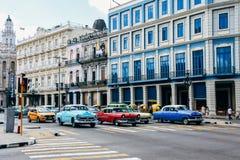 Färgrika klassiska bilar kör förbi gamla färgrika byggnader i havannacigarren, Kuba royaltyfri foto