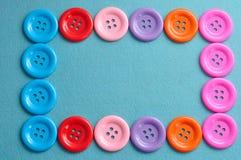 Färgrika knappar som bildar en gräns Arkivbild