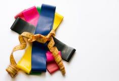 Färgrika konditiongummin som binds upp med meterbandet som isoleras på vit bakgrund Sportbegrepp - elastiska expanders av olika f royaltyfria bilder
