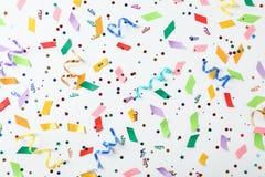 Färgrika konfettier och banderoller på vit bakgrund Arkivbild