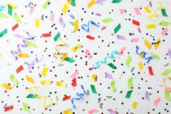 Färgrika konfettier och banderoller på vit bakgrund Royaltyfri Bild