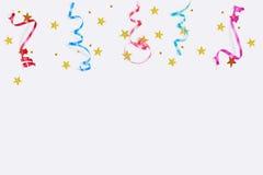 Färgrika konfettistjärnor, banderoller på en ljus bakgrund Arkivbild