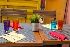 Färgrika koppar och servetter på tabellen Arkivfoto