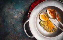 Färgrika kryddor i skedar på tappningmetallplattan för orientalisk eller indisk kokkonst för asiat, arkivbilder