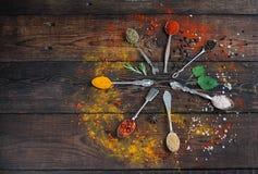 Färgrika kryddor i tappningsilverskedar på lantlig träbakgrund, bästa sikt Royaltyfri Foto