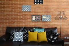 Färgrika kuddar på en soffa med tegelstenväggen arkivbild