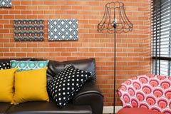Färgrika kuddar på en soffa med tegelstenväggen royaltyfri fotografi