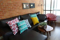 Färgrika kuddar på en soffa med tegelstenväggen Arkivbilder