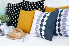 Färgrika kuddar på en soffa med vit tegelstenvägg I royaltyfri foto