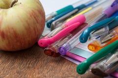 färgrika kulspetspennor och äpplet på anmärkningsboken uppvaktar på Fotografering för Bildbyråer