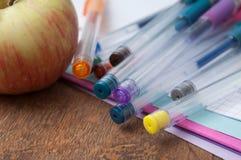 färgrika kulspetspennor och äpplet på anmärkningsboken uppvaktar på Royaltyfria Foton
