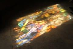 Färgrika ljusa fläckar på det belade med tegel golvet arkivbilder