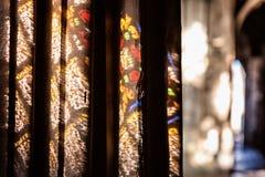 Färgrika ljusa fläckar på väggen i kyrkan Solljus som filtreras till och med målat glassfönstret arkivbilder