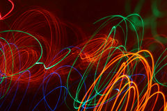 Färgrika ljusa strålar som drar abstrakt begreppmodellerna i mörkret Stock Illustrationer