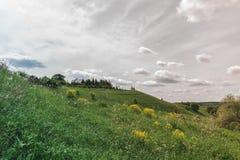 F?rgrika ljusa Sunny Landscape med det ryska land-huset p? kullen i en mitt av fotoet med en molnig himmel f?r ljus kontrast royaltyfri foto