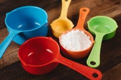 Färgrika mäta koppar med mjöl på trätabellen royaltyfri fotografi