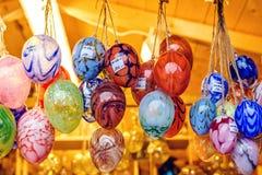 Färgrika målade exponeringsglasprydnader i form av ägg som hänger för sal royaltyfria bilder