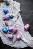 Färgrika målade fega ägg för påsk med servetten på mörk bakgrund royaltyfri foto