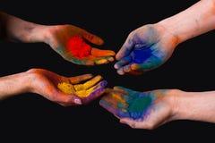 Färgrika målade händer, hållande holi som isoleras royaltyfri fotografi