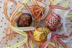 Färgrika målade påskägg på den prickiga bordduken som täckas med ljusa färgrika band, traditionell härlig påskstilleben royaltyfria bilder
