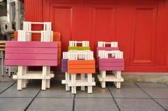 Färgrika målade trätabeller och stolar Arkivfoton