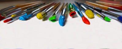 Färgrika målarfärgborstar som ut läggas Fotografering för Bildbyråer