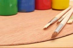 Färgrika målarfärger och borstar royaltyfria foton