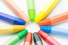 Färgrika mångfärgade pastellfärgade vaxfärgpennor som är ordnade i cirkel på vitbok Dra tillbaka till hobbyen för teckningen för  arkivfoto