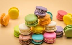 Färgrika Macaron som är söt och som är läcker på kräm- färgbakgrund Arkivfoton