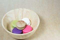 Färgrika macarons i träbunke Arkivbilder