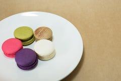 Färgrika macarons på den vita maträtten Arkivbild