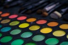 Färgrika makeupprodukter och borstar som förläggas på ett bräde Arkivfoton