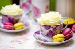 Färgrika makron - guling och rosa färger - på plattor med koppar med vita rosor Royaltyfria Bilder