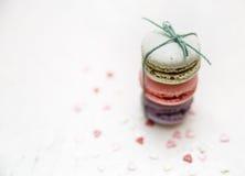 Färgrika makron med liten hjärta formar godisar på vit bakgrund Royaltyfri Bild