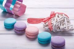 Färgrika makron med träbakgrund för vit trähjärtaovewhite valentin för dag s Royaltyfria Foton