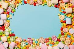 Färgrika marshmallowgodisar och geléer som bakgrund Arkivbild
