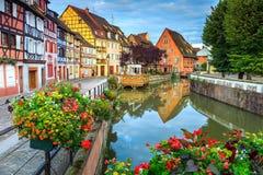 Färgrika medeltida korsvirkes- fasader som reflekterar i vatten, Colmar, Frankrike royaltyfria bilder