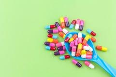 Färgrika medicinkapslar med skeden Arkivfoton